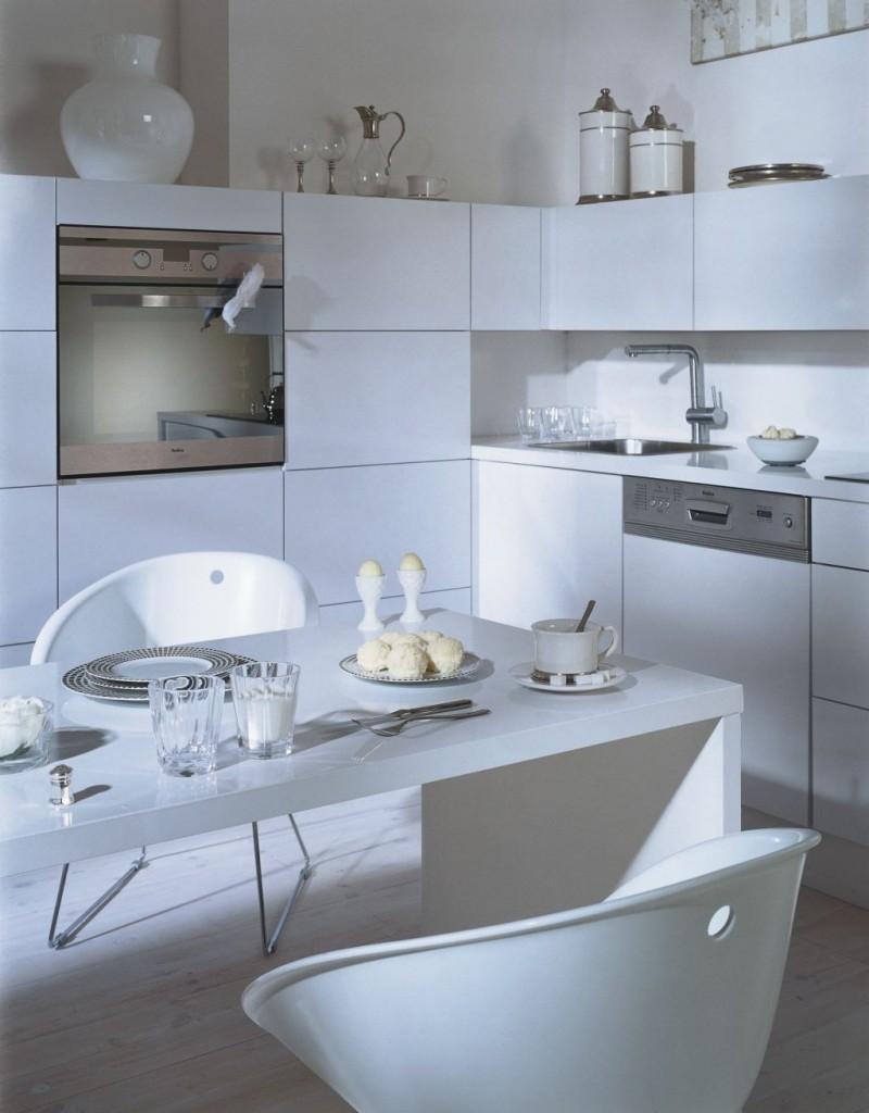 aranżacja kuchni białej ze stołem i niskiem słupkiem